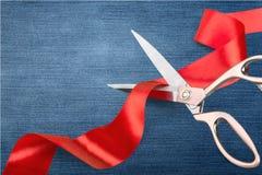 Schaar die rood lint, close-upmening op blauw snijden royalty-vrije stock foto's