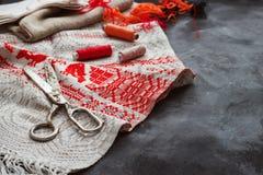 Schaar, spoelen met draad en naalden, gestreepte stof Oude naaiende hulpmiddelen op de achtergrond Uitstekende achtergrond Stock Foto
