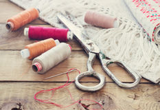 Schaar, spoelen met draad en naalden, gestreepte stof Oude naaiende hulpmiddelen op de oude houten achtergrond wijnoogst Stock Afbeeldingen