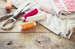 Schaar, spoelen met draad en naalden, gestreepte stof Oude naaiende hulpmiddelen op de oude houten achtergrond wijnoogst Royalty-vrije Stock Afbeeldingen
