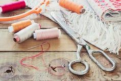 Schaar, spoelen met draad en naalden, gestreepte stof Oude naaiende hulpmiddelen op de oude houten achtergrond wijnoogst Royalty-vrije Stock Foto's
