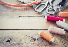 Schaar, spoelen met draad en naalden, gestreepte stof Oude naaiende hulpmiddelen op de oude houten achtergrond wijnoogst Royalty-vrije Stock Fotografie