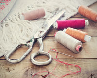 Schaar, spoelen met draad en naalden, gestreepte stof Oude naaiende hulpmiddelen op de oude houten achtergrond wijnoogst Royalty-vrije Stock Foto