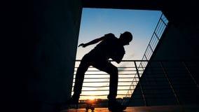 Schaatser die op een raad op een zonsondergangachtergrond springen, langzame motie stock footage