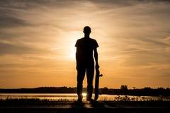 Schaatser die zich op weg tegen de zonsondergang bevinden en een skateboard in één hand houden stock foto