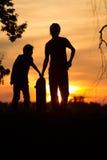 Schaatsers bij zonsondergang Stock Foto's