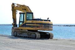 Schaberbagger, der den Strand durch das Meer schattiert lizenzfreies stockbild