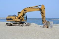 Schaberbagger, der den Strand durch das Meer schattiert stockbilder