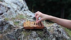 Schach auf dem Stein draußen spielen stock footage