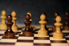 Schach stellt auf einem Schachbrett auf einem dunklen Hintergrund dar Stockbilder