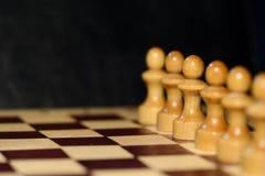 Schach stellt auf einem Schachbrett auf einem dunklen Hintergrund dar Stockfoto