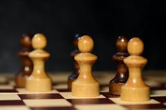 Schach stellt auf einem Schachbrett auf einem dunklen Hintergrund dar Lizenzfreies Stockfoto