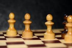 Schach stellt auf einem Schachbrett auf einem dunklen Hintergrund dar Lizenzfreies Stockbild