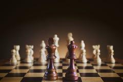Schachbrett mit hölzernen Zahlen, schwarzes Schach stellt auf Vordergrund dar Stockbild