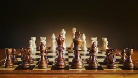 Schachbrett mit hölzernen Zahlen, schwarzes Schach stellt auf Vordergrund dar Stockfotografie
