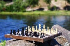 Schachbrett mit Schachfiguren auf Felsen mit Flussdammrückseite Stockbilder