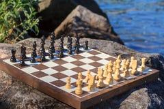 Schachbrett mit Schachfiguren auf Felsen mit Flussdammrückseite Lizenzfreie Stockfotos