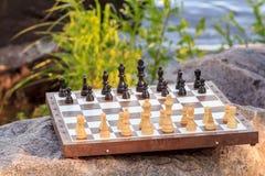 Schachbrett mit Schachfiguren auf Felsen mit Flussdammrückseite Lizenzfreie Stockfotografie