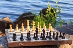 Schachbrett mit Schachfiguren auf Felsen mit Flussdammrückseite Lizenzfreies Stockfoto