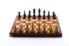 Schachbrett mit Schwarzweiss-Figürchen auf einem weißen Hintergrund lizenzfreie stockfotos