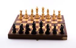 Schachbrett mit Schwarzweiss-Figürchen auf einem weißen Hintergrund lizenzfreie stockfotografie