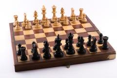 Schachbrett mit Schwarzweiss-Figürchen auf einem weißen Hintergrund stockfotografie