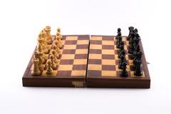 Schachbrett mit Schwarzweiss-Figürchen auf einem weißen Hintergrund stockbild