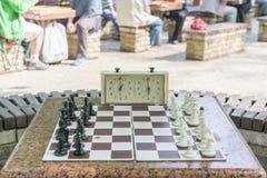 Schachbrett mit St?cken und Uhr auf h?lzernem Schreibtisch in Zusammenhang mit dem Schachturnier Schachturnier mit Schachuhr an lizenzfreie stockfotografie