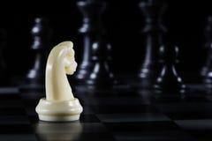 Schachfigur des weißen Ritters auf schwarzem Hintergrund Lizenzfreie Stockfotos