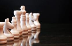 Schachfiguren auf Dunkelheit Stockbild