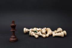 Schachfiguren auf einem schwarzen Hintergrund Der König steht nahe bei den besiegten weißen Zahlen Stockfotos