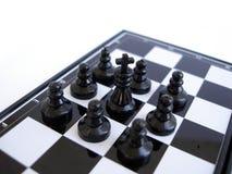 Schachkönig steht auf einem Schachvorstand mit Abbildungen Stockfotografie