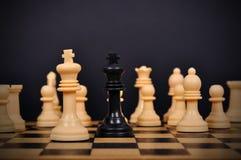 Schachkönig umgeben lizenzfreie stockbilder