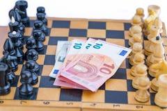 Schachkomponenten und -geld zwischen ihnen Stockfotografie