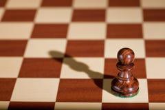 Schachstück - ein schwarzer Pfandgegenstand auf einem Schachbrett. stockfotos