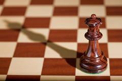 Schachstück - eine schwarze Königin auf einem Schachbrett. Stockbild