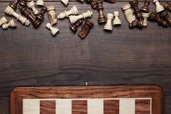 Schachvorstand und -abbildungen woden ein Hintergrund Stockfoto