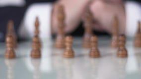 Schachwettbewerb, Mann in beweglichem Pfand der Klage auf Schachbrett, unternehmerische Entscheidung stock footage