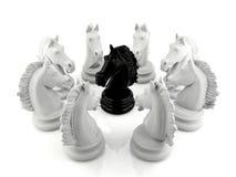 Schack för svart riddare som omges av en grupp av schack för vit riddare Arkivbild