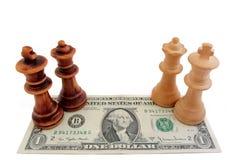 Schack och dollar: Ljus och mörk konung och drottning på en US dollarräkning Arkivbild