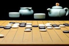 Schackbräde och teservis Arkivbild
