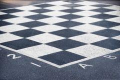 Schackbräde på asfalt arkivfoto