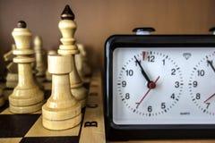 Schackbräde, schackstycken och schackklocka Arkivfoto
