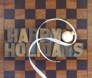 Schackbräde med lyckliga ferier och prydnaden Royaltyfri Fotografi