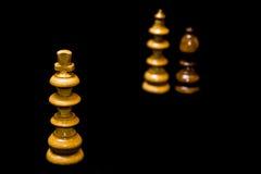 Schackdrottning som fuskar konungen som isoleras på svart Royaltyfri Bild