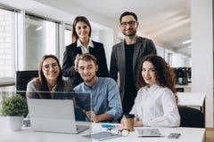 Schacket figurerar bishops Unga idérika coworkers som arbetar med nytt startprojekt i modernt kontor och ser kameran royaltyfri foto