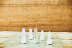 Schackexponeringsglas ombord i lek På tappningträgolvbakgrund skrapade en tappning gamla filmfärger Begreppskonkurrensaffär Royaltyfria Bilder