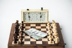 Schackklocka nära schackbräde med diagram och isolerade dollarsedlar på vit Arkivbilder
