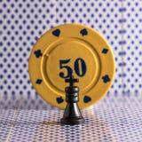 Schackkonung mot bakgrunden av pokerchiper Arkivbilder