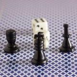 Schackkonungen på en suddig bakgrund av annan figurerar och tärning Royaltyfri Bild